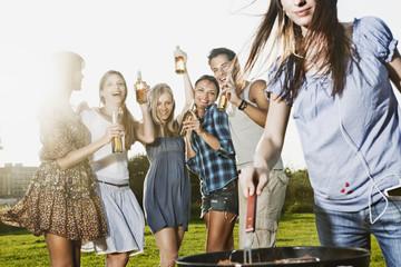 Deutschland, Köln, Frau, Grillen mit Freunden im Hintergrund