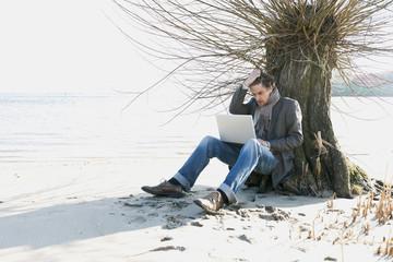 Deutschland, Hamburg, Mann sitzt neben Baum mit Laptop
