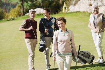 Italien, Kastelruth, Frau mit Golfer im Hintergrund auf Golfplatz