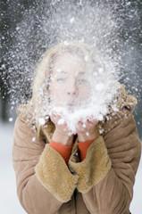 Österreich, Salzburger Land, Altenmarkt, Junge Frau bläst Schnee aus der Hand