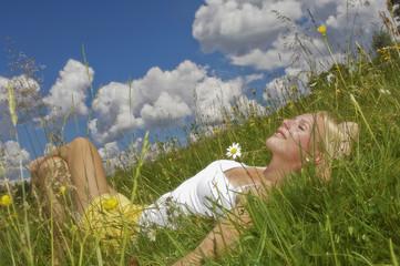 Österreich, Salzburger Land, Altenmarkt, Junge Frau liegt auf einer Wiese, die Augen geschlossen