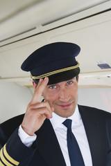 Deutschland, Bayern, München, Pilot salutiert in der Business Class Flugzeugkabine, Lächeln