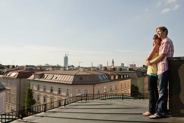 Deutschland, Bayern, München, Junges Paar genießt auf der Dachterrasse mit Stadt im Hintergrund