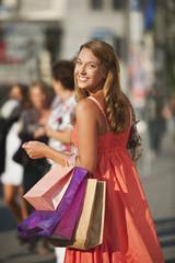 Deutschland, München, Karlsplatz, junge Frau mit Einkaufstüten
