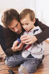 Vater und Sohn spielen mit Spielzeug-Rennstrecke