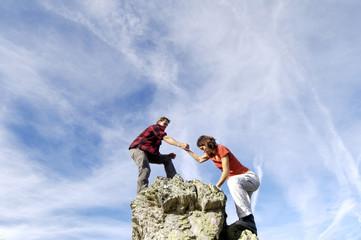 Junges Paar klettert auf Gipfel, Mann hilft Frau