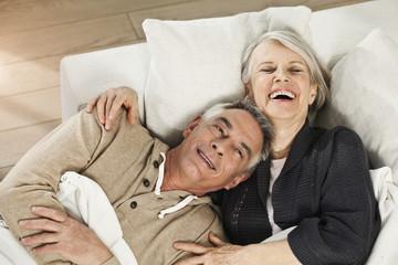 Deutschland, Berlin, älteres Paar, Senioren liegend auf der Couch