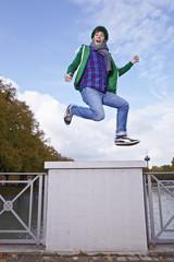 Deutschland, Köln, junge Mann springt auf Brücke