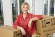 Deutschland, Bayern, Gröbenzell, erwachsene Frau mit Kartons, Lächeln