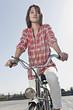 Deutschland, Berlin, Junge Frau mit Fahrrad steht auf Parkebene