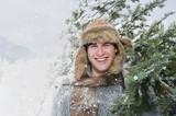 Österreich, Land Salzburg, Flachau, Junger Mann mit Weihnachtsbaum im Schnee