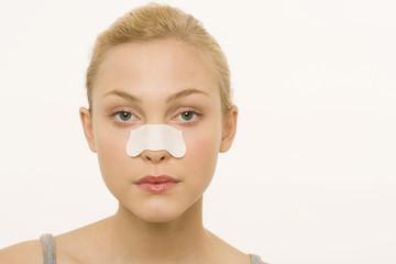Frau trägt ein Pflaster über der Nase