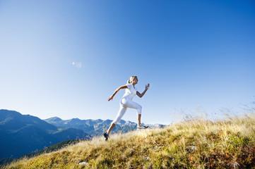 Österreich, Salzburger Land, Junge Frau läuft auf Bergwiese