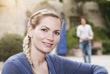 Italien, Toskana, Magliano, junge Frau und Mann im Hintergrund