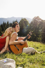 Junges Paar auf der Wiese sitzt, Mann spielt Gitarre