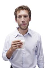 Junger Mann hält ein Glas Milch
