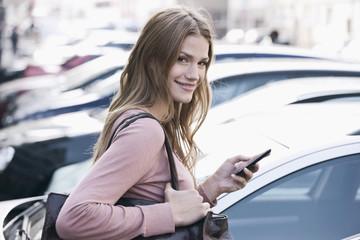 Deutschland, Köln, Junge Frau mit Telefon in der Nähe Parkplatz