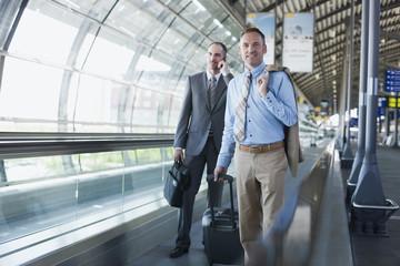 Deutschland, Leipzig-Halle, Flughafen, zwei Geschäftsleute auf Transportband, Rollband, Fahrsteig