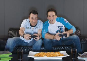 Männer sitzen auf der Couch und spielen Videospiele