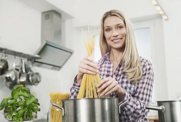 Deutschland, Köln, Frau kocht Spaghetti