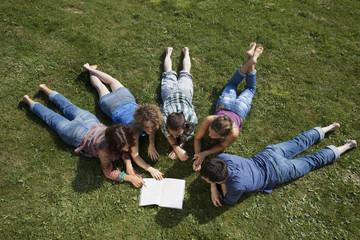 Deutschland, München, Mann und Frau, die auf Gras-und Lesebuch