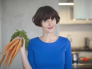 Deutschland, Köln, Junge Frau mit Karotten in Küche, Lächeln
