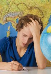 Teenage Junge mit Globus und Landkarte