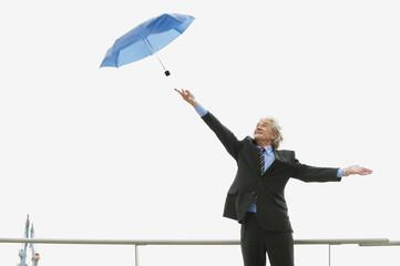Deutschland, Hamburg, Geschäftsmann versucht Regenschirm zu fangen
