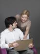 Mann und Frau lächelnd mit einem Laptop