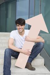 Deutschland Nordrhein-Westfalen, Düsseldorf, Junger Mann sitzt auf Stufen mit Pfeil nach oben