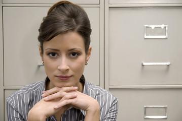 Junge Frau sitzt vor Aktenschrank