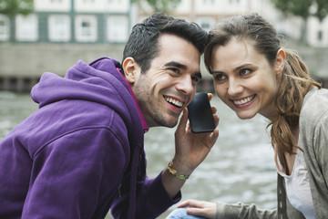 Deutschland, Berlin, Paar mit Handy auf Flussufer