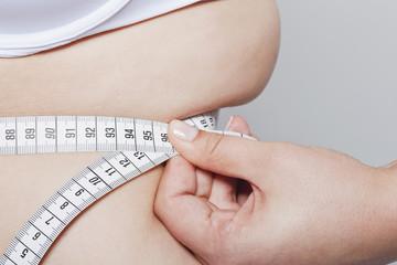 Deutschland, Köln, Junge Frau Messung ihrer Taille mit Maßband