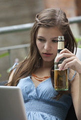 Deutschland, Berlin, Nahaufnahme der jungen Frau mit Laptop und Bierflasche