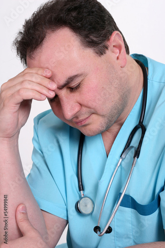 Stressed young male medical professional in blue scrubs touching