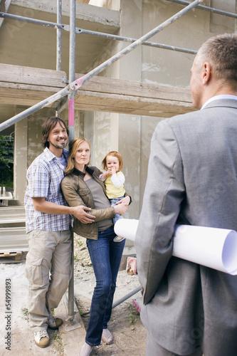 Architekt und junge Familie auf der Baustelle