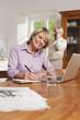 Deutschland, Kratzeburg, erwachsene Frau schreibt etwas, erwachsener Mann am Telefon im Hintergrund
