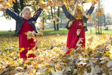 Zwillinge spielen mit Herbstlaub