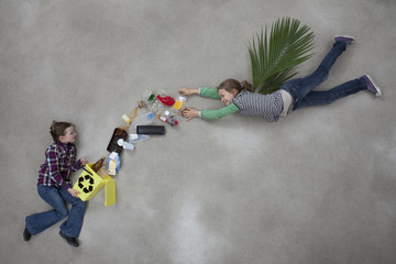 Junge hält Mülleimer und Mädchen wirft Müll