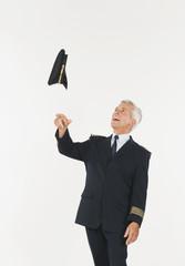 Älterer Pilot wirft Mütze vor weißem Hintergrund