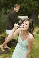 Junges Paar, Frau putzt sich die Zähne