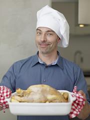 Deutschland, Köln, Erwachsene mit gebratenem Huhn, Lächeln