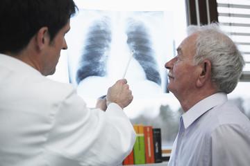 Deutschland, Hamburg, Arzt und Patient mit Röntgenbildern in der Klinik