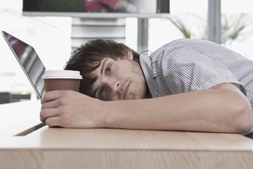 Deutschland, Köln, Junger Mann liegend auf dem Tisch mit Laptop und Tasse