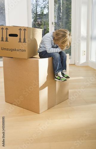 Deutschland, Bayern, Gröbenzell, Junge sitzt auf Karton
