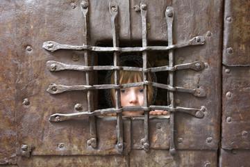 Italien, Südtirol, Potrait eines Mädchens hinter Gittern