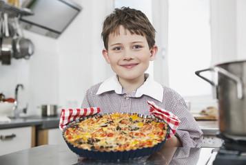 Deutschland, Köln, Junge hält eine Pizza