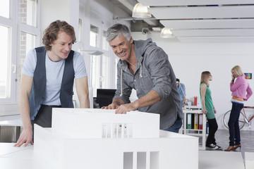 Deutschland, Bayern, München, Männer betrachten Architekturmodell im Büro, Kollegen im Hintergrund