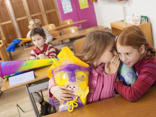 Mädchen mit Schultüte flüstern im Klassenzimmer