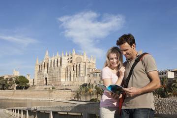 Spanien, Mallorca, Palma, Paar sucht in Reiseführer mit St. Maria Kathedrale im Hintergrund